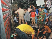 ?? KHALID MOHAMMED / AP ?? Damage is assessed at the blast-hit market in Sadr City, Iraq, on Monday.