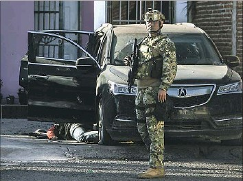 ?? Rashide Frias Associated Press ?? A MEXICAN MARINE stands near the body of a gunman last month in Culiacan, Sinaloa state. Authorities said heavily armed men attacked the patrolling troops, starting a gunfight that left one marine dead.