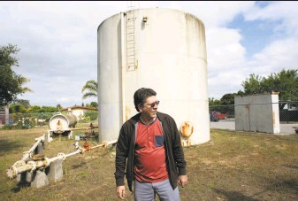 ?? Photos by Santiago Mejia / The Chronicle ?? Horacio Amezquita, general manager of San Jerardo Cooperative, walks by an outdated water system. The community is on its fourth well since 1990, due to pollutants in the first three.