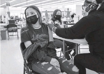 ?? TNS pHOtO ?? JUST A PINCH: Luscia Castellanos, 12, of Des Plaines, Ill., looks away as she receives a Pfizer COVID-19 vaccine from a nurse at a Cook County vaccine site. Children ages 12 to 15 are now eligible to receive COVID-19 vaccines.