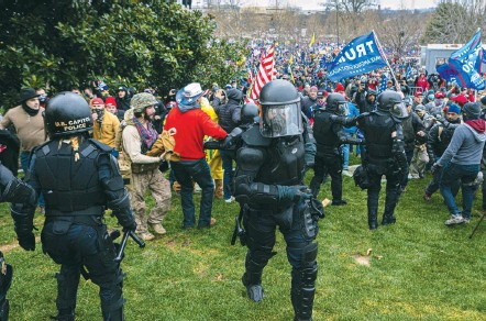 ?? MICHAEL NIGRO/SIPA USA/ASSOCIATED PRESS ?? Capitol Police move back Wednesday as pro-trump supporters flood Capitol grounds. Outgoing Capitol Police Chief Steven Sund said in an interview that his supervisor­s were reluctant to take formal steps to put the D.C. National Guard on call.