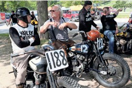 ?? MICHAEL SEARS / MILWAUKEE JOURNAL SENTINEL ?? Chris McGregor (left) of Oklahoma City, Oklahoma, on his 1942 Harley-Davidson WLA, and Kem Runnebacke of New Bern, North Carolina, on his 1937 Harley-Davidson WLD, discuss the race course and bikes as they wait for their turn on the oval.