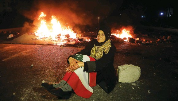 ?? (Mohamed Azakir/Reuters) ?? A WOMAN sits near a fire during a protest in March in Beirut against the fall in the Lebanese currency and mounting economic hardship.