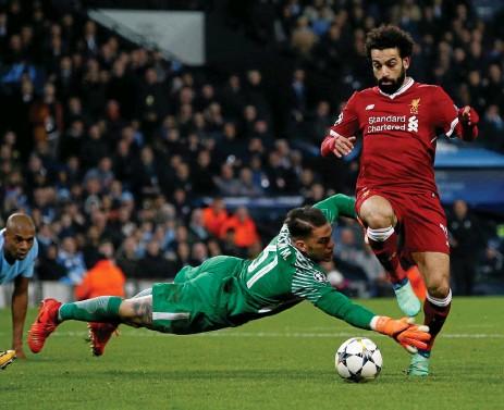 ?? Bild: ANDREW YATES ?? MÄSTERLIGT. Liverpools Mohamed Salah rundar Manchester Citys målvakt Ederson och rullar in ett av målen i vårens möte mellan lagen i Champions League. Då vann Liverpool. Ligan vann City. Nu möts de igen i en tidig seriefinal i Premier League.
