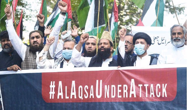 ?? Agence France-presse ?? ↑ Protesters raise slogans during a demonstration against air strikes launched on Gaza in Karachi on Tuesday.