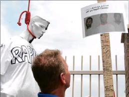 ??  ?? A man reads an anti-crime poster erected near a makeshift gallows during a protest recently. A reader has called for murderers to pay the ultimate price for their deeds. PICTURE: ZANELE ZULU