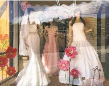 ?? Suman Naishadham / Associated Press ?? Mannequins in wedding gowns are seen in a window at a bridal store in Nogales, Ariz., that has been closed for nearly a year due to the pandemic. Couples are now racing to the altar.