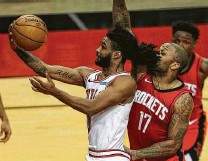 ?? Yi-Chin Lee / Staff photographer ?? The Bulls' Coby White works his way past the Rockets' P.J. Tucker, who started at center for the first time this season.