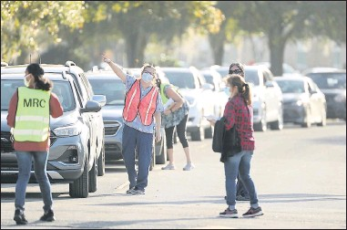 ?? THE ORLANDO SENTINEL ?? Workers directed traffic toward a COVID-19 vaccination site at Lake-Sumter State College in Leesburg, Fla., on Friday. The Lake County vaccineswere being given to people who are 65 years and older aswell as front-line workers.