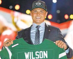 ?? AP & BYU ATHLETICS ?? Former BYU quarterback Zach Wilson, who got his Jets jersey last week, has spent several summers working camps in Harlem (photo r.) and was known around his old school as someone with a big heart.