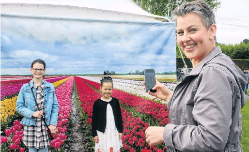 ?? PHOTOS: LUISA GIRAO ?? Transported by tulips . . . (clockwise from above) Anna Murdoch takes a picture of Emily Irvine (11, left) and Mia Murdoch (6) at the Triflor's tulip farm open day in Edendale yesterday; event committee member Jean Kirby poses with her favourite tulip ''Foxtrot''; Jill Hill and Karen Brier select the tulip bulbs they will plant in their garden for next spring.