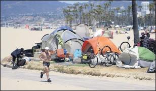 ?? MARCIO JOSÉ SÁNCHEZ ?? A jogger walks past a homeless encampment on June 8, 2021, in the Venice Beach section of Los Angeles.