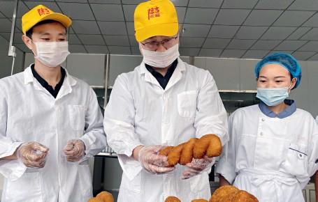 ??  ?? 杨坤龙(中)在检查刚生产的麻花产品
