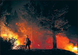 ?? Wally Skalij Los Angeles Times ?? FIREFIGHTERS work on the Caldor fire near Lake Tahoe on Sept. 2. Flames have reached above 8,000 feet, searing terrain that was once too wet to burn.