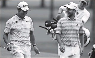 ?? CURTIS COMPTON | Atlanta Journal-Constitution ?? Japan's Hideki Matsuyama, far left, and Xander Schauffele share a laugh after they both make eagle putts on the 15th green during the third round. Schauffele, a San Diego native whose mother was raised in Japan, speaks some Japanese, making for a comfortable pairing with Matsuyama.