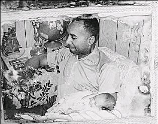 ?? Family photo ?? Grandfather: Edgar Hollingsworth holds his eldest grandchild, Wesley Jr., in a photo taken about 20 years ago thatwas found, stained and damaged, in his home. Edgarwas rescued Sept. 13 and died two days later.