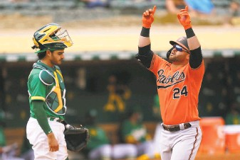 ?? Daniel Shirey / Getty Images ?? Baltimore's DJ Stewart celebrates his tworun home run at the Coliseum in the sixth inning as A's catcher Aramis Garcia regroups. It was the Orioles' only extrabase hit in the game.