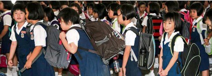 ??  ?? Carrying heavy bags on their backs over a period of time can damage children's posture and their spinal cord. – File photo
