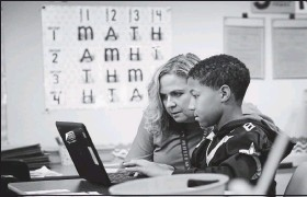 ?? DEAN HOFFMEYER/TIMES-DISPATCH ?? Kim Powell, principal of Sandston Elementary School, helped fourth-grader Brayden Green with his classwork in November 2019.
