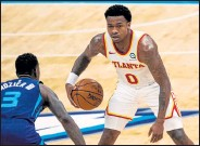 ?? JACOB KUPFERMAN / Getty Images ?? The Hawks' Brandon Goodwin, right, brings the ball up court while being guarded by the Hornets' Terry Rozier on Sunday at Spectrum Center, in Charlotte, N.C.