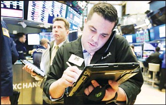 ??  ?? Trader Joseph Lawler (right), works on the floor of the New York Stock Exchange. (AP)