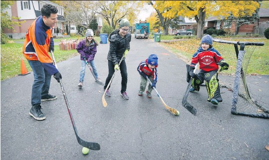 ?? JOHN MAHONEY ?? Just for fun: Jason Duke plays road hockey with his children, from left, Clara, Ella, Lennon and Nolan outside their home in Pointe-Claire.
