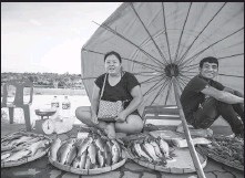 ?? PHOTOS BY KAI QIAO / XINHUA ?? Right: Fish is sold at an open-air market in Vientiane.