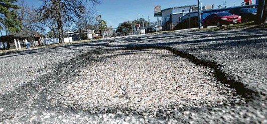 ?? Yi-Chin Lee / Staff photographer ?? A pothole lies Friday along 20th Street between Durham and Shepherd drives near the Heights. Last week's freeze is likely to worsen potholes, experts say.