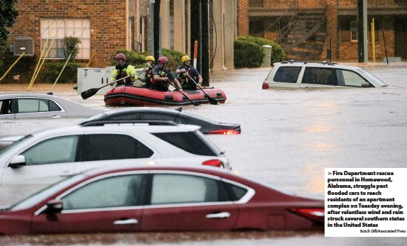 ?? Butch Dill/Associated Press ?? Fire Department rescue personnel in Homewood, Alabama, struggle past flooded cars to reach residents of an apartment complex on Tuesday evening, after relentless wind and rain struck several southern states in the United States