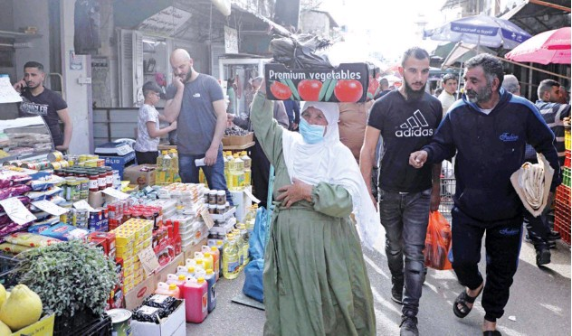 ?? Agence France-presse ?? ↑ People walk past Palestinian vendors at the old market in the West Bank city on Sunday.