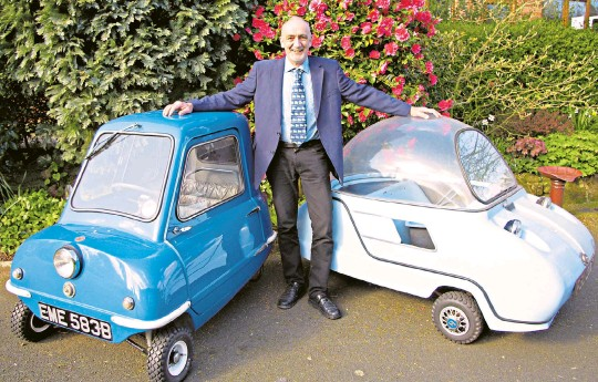 ??  ?? g Andy Carter is a microcar enthusiast who now owns four such vehicles; pictured here with a Peel P50, on the left, and a Trident