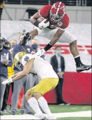 ?? THE ASSOCIATED PRESS ?? Alabama's Najee Harris takes flight to hurdle Notre Dame's Nick McCloud in the first half. The Crimson Tide advanced to the CFP title game for the fifth time in the series' seven seasons.