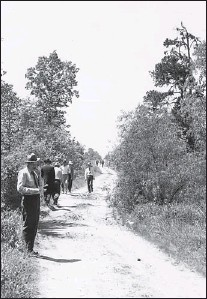 ?? Photos courtesy of Tillman Johnson family ?? Left: Law officers search along North Park Road in April 1946 for clues in the Phantom Killer's third attack. Paul Martin, 16, and Betty Jo Booker, 15, were killed early Sunday morning, April 14, 1946, in wooded areas north and west of Spring Lake Park.