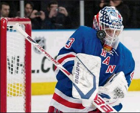 ??  ?? New York Rangers goalie Martin Biron takes the puck on his mask as he makes a save against the San Jose Sharks during first-period NHL action at Madison Square Garden in New York Monday. New York won the game 5-2.