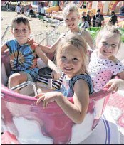 ?? PHOTO: Coral Cooksley ?? TEA CUP SMILES: Howlong's Mason Miller (left), Maddison Smith, Alice Miller and Darcy Smith had fun in the cup and saucer ride - one many of childrens activities in the police paddocks on Easter Saturday at the Golden Horse Shoes Festival.