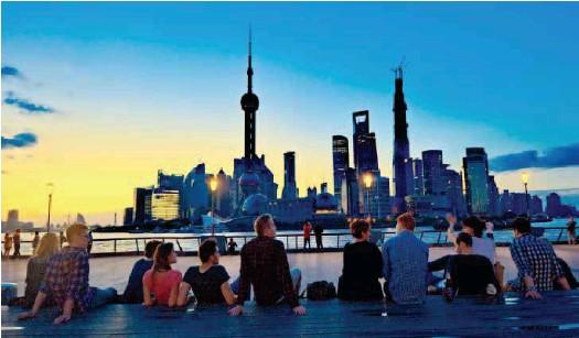 ??  ?? Инициатива «Пояс и путь» приносит странам мира исторические возможности. По мере расширения открытости в Китай приезжает все больше иностранцев. На снимке: иностранцы на шанхайской набережной (фото CFP)