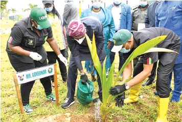 ??  ?? Lagos State Governor, Mr. Babajide Sanwo- Olu ( middle) planting a tree to mark the State's Y2021 Tree Planting Day, assisted by the Commissioner for the Environment and Water Resources, Tunji Bello ( right) and General Manager, Lagos State Parks and Gardens Agency ( LASPARK), Mrs. Adetoun Popoola at the Year 2021 Tree Planting Day in Lagos.