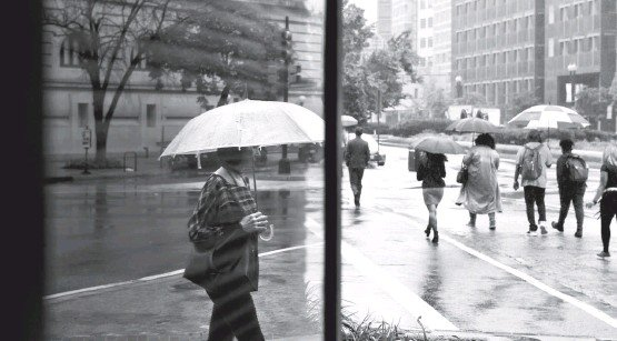 ?? KATHERINE FREY/THE WASHINGTON POST ?? Pedestrians, some of them reflected in a window, navigate the puddles during Monday's rain in the District. The next predicted chance for rain is Thursday.