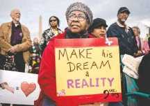 """??  ?? Eleanor Young, from Columbus, Ohio, holds a sign referencing the Rev. Martin Luther King Jr.'s """"I Have a Dream"""" speech on the anniversary of his death."""