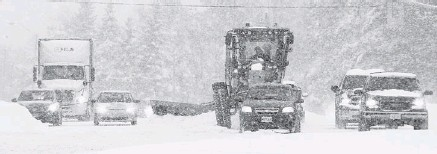 ?? PHOTOS: JULIE OLIVER/OTTAWA CITIZEN ?? Even with a big plow, the operator of this road grader finds it hard to keep Bronson Avenue clear of heavily falling snow.