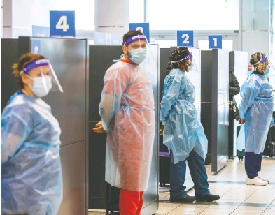 ?? CARLOS OSORIO / REUTERS FILES ?? Health-care workers prepare to test passengers at Toronto's Pearson airport last week.