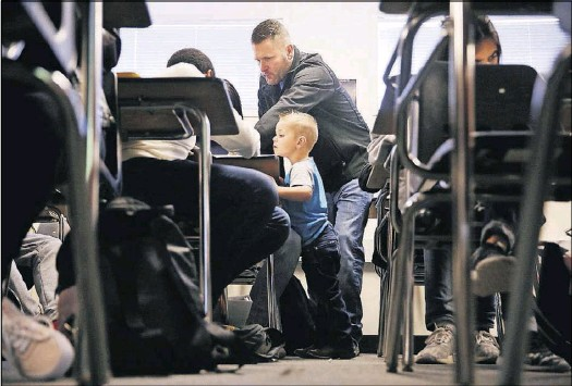 ?? Andy Jacobsohn/Staff Photographer ?? Gary Don Moore instructs students at Plano East as his son, Gary Autry, 3, watches. Moore, an assistant football coach and math teacher, has been diagnosed with amyotrophic lateral sclerosis, a disease with no known cure.