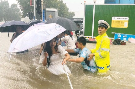 ?? CHINA DAILY/REUTERS ?? An officer helps residents in Zhengzhou. The floods, which have killed 25, prompted President Xi Jinping to issue an order through state media for officials to give top priority to people's safety and property. The rain began over the weekend and continued Wednesday.