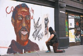 ?? Yalonda M. James / The Chronicle ?? Taylor Ross honors George Floyd by placing flowers and a candle before an Oakland mural of the police shooting victim after a jury convicted his killer.