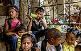 ??  ?? Children wait to eat lunch at Alimenta La Solidaridad's soup kitchen. Oil sanctions could lead to a 26 percent reduction in the size of Venezuela's economy, which is already just half as big as it was in 2013, the year when Maduro took power.
