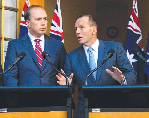 ??  ?? DANGEROUS PLAN: Allowing Immigration Minister Peter Dutton (left, with Prime Minister Tony Abbott) to unilaterally declare someone a non-citizen would effectively elevate one man to the status of judge, jury and executioner of identity.