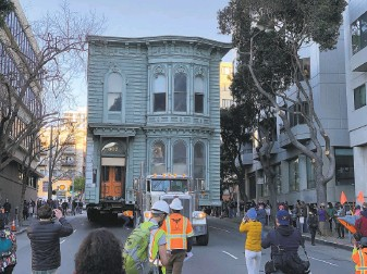 ?? Stephen Lam / The Chronicle ?? A crowd follows a Victorian home as it parades the wrong way down the street to its new home at a top speed of 1 mph. It was the first time such a home was relocated in S.F. in 50 years.