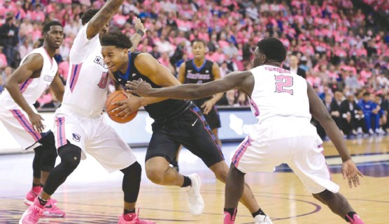?? | NATI HARNIK/ AP ?? DePaul's Eli Cain drives to the bas­ket be­tween Creighton's Mar­cus Fos­ter ( 0) and Khyri Thomas. The Blue Demons lost their fourth con­sec­u­tive game Satur­day.