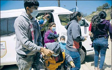 ?? Photographs by Alejandro Tamayo San Diego Union-Tribune ?? MANY EXPELLED families end up at Templo Embajadores de Jesus, a church shelter in a canyon in Tijuana once known for housing Haitian migrants. Above, a Mexican government van drops off a group last week.