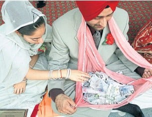 ?? ANDREW STAWICKI TORONTO STAR FILE PHOTO ?? In Sikh weddings, like these 2002 Mississauga nuptials, money has an open place in the ritual, with bills here being deposited by guests into the bride's scarf (known as a pala).